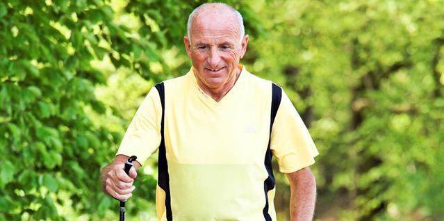 Eldre mann går tur med staver
