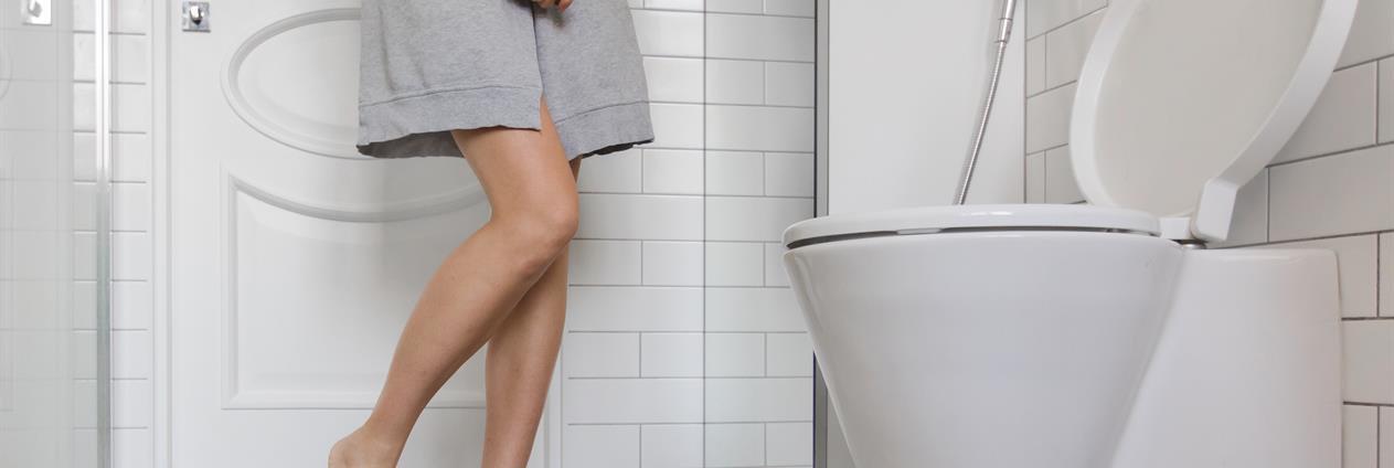 Kvinne i morgenkåpe står ved siden av et toalett. Foto.