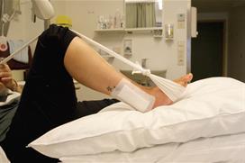 Fot med operert ankel og bøyd kne og strammet bånd. Foto
