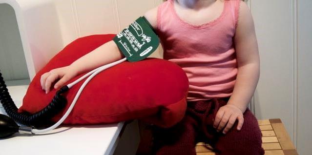 Jente med mansjett på armen for blodtrykksmåling. Foto