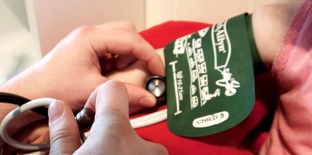 Måling av blodtrykk på barn, lytter med stetoskop på arm. Foto