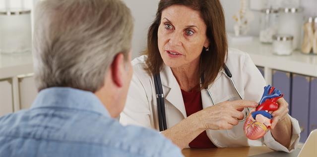 Lege viser pasient en medell av hjerte