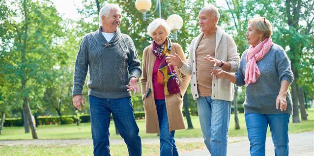Fire eldre mennesker går tur i parken