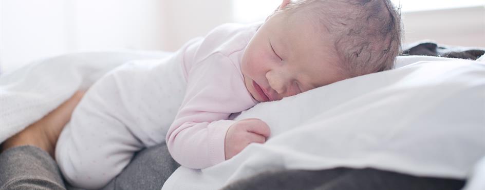 Baby hviler på pappas bryst. Foto