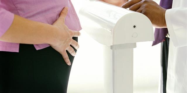 Gravid kvinne står på vekt