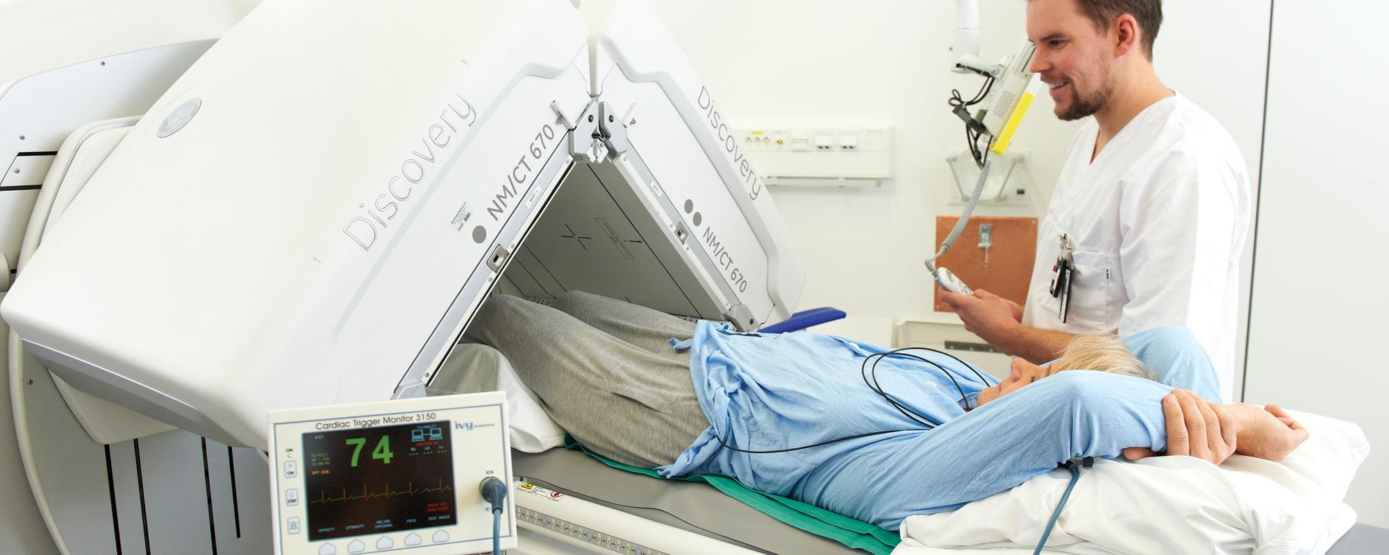 Operatør sammen med pasient som gjøres klar for SPECT/CT