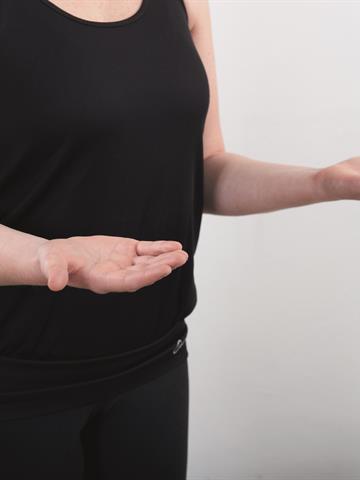 Hold overarmene inntil kroppen. Vri underarmen vekselsvis, slik at håndflaten vender opp mot taket og ned mot gulvet.
