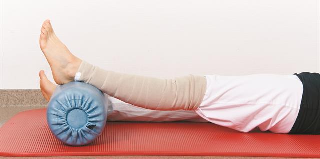 Legg en fast pute under ankelen slik at kneleddet kommer opp fra underlaget. Det skal tøye i knehasene.