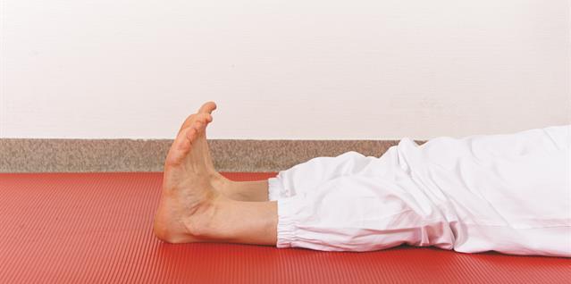 Ligg med strake ben. Bøy og strekk godt opp og ned i anklene.