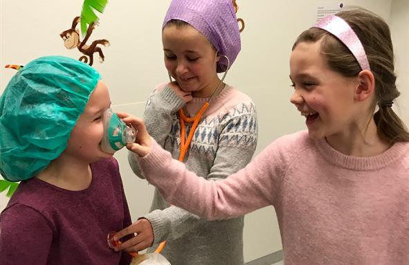 Tre jenter leiker med oksygenmaske og stetoskop.