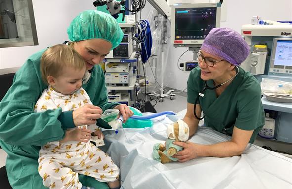 Eit lite barn sit på fanget til mor si inne på operasjonsstova mens han får sjå og ta på maska som han skal puste i.