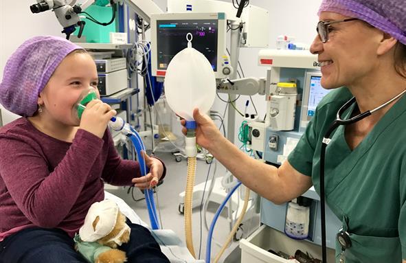 Ei jente på operasjonsstova pustar i ei maske. Anestesisjuk held ein ballong som ein blåser opp når ein pustar i maska.