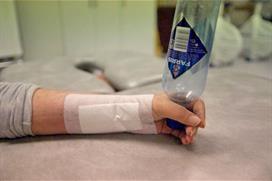 Hånd holder flaske og roterer. Foto
