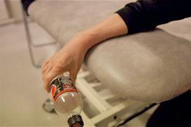 Avspent hånd holder halvlitersflaske utfor bordkant. Foto