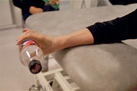 Hånd holder flaske utfor bordkant. Foto