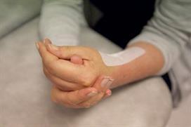 Frisk hånd hjelper oprert hånd med å knyte hånden. Foto