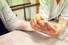 Fysioterapeut behandler hånden til pasient. Foto