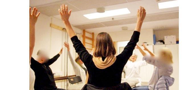 Gruppe pasienter sitter i ring, strekker armene opp i været. foto