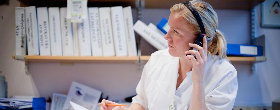 Jordmor snakker i telefonen på kontor. Foto