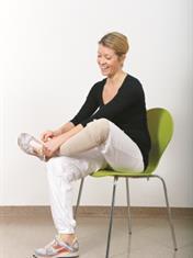 Sitter på stol og knyter lisse