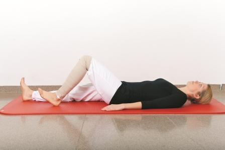 Ligg på ryggen. Bøy det opererte benet, og trekk det mot deg, samtidig som du fører hælen langs underlaget.